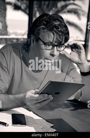 B&W Mann im Urlaub Einstellung überrascht von Bildschirminformationen Kleingedruckte auf seinem iPad Air Tablet - Stockfoto