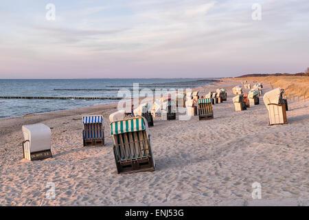 Liegestühle am Strand mit Dünen an der Ostsee in Deutschland bei Sonnenuntergang - Stockfoto