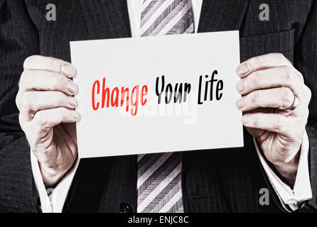Ein Geschäftsmann hält eine Visitenkarte mit den Worten: Change Your Life, darauf geschrieben. - Stockfoto