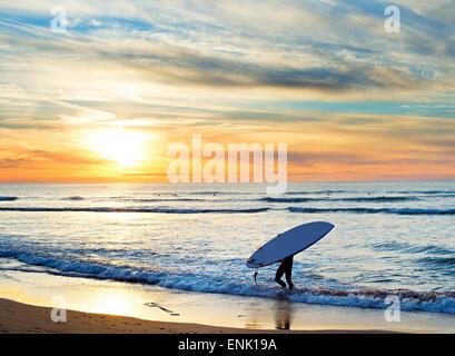 Mann mit Surfbrett am Strand bei Sonnenuntergang. Die Region Sagres, Algarve, Portugal - Stockfoto