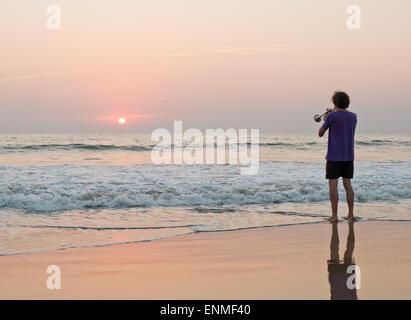 Ein Mann, eine Trompete auf Agonda Beach Goa in Indien bei Sonnenuntergang - Stockfoto