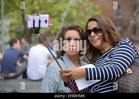 Zwei Frauen Touristen ein Selbstporträt in der Nähe von dem Brunnen im Washington Square Park in Greenwich Village, - Stockfoto