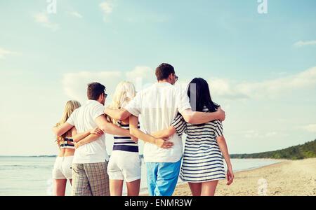 lächelnden Freunde umarmen und zu Fuß am Strand - Stockfoto