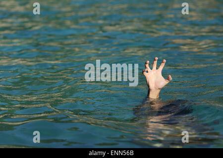 Hand des Menschen ertrinken im Meer an einem sonnigen Tag - Stockfoto