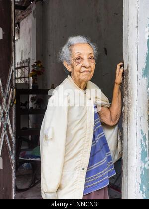 Afro-kubanische Senior Bürgerin mit grauen Haaren Stand in der Tür ihres Hauses schauen, einen Arm gegen die Tür - Stockfoto