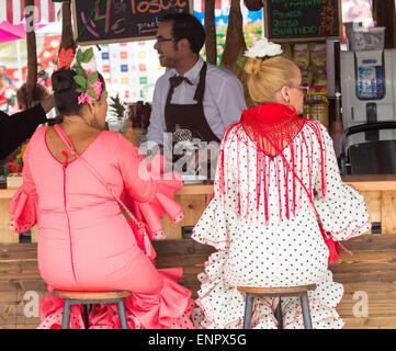 Flamenco Tänzerinnen und Tänzer in tigh Kleider sitzen auf Barhockern an der Feria de Abril Fiesta in Spanien - Stockfoto