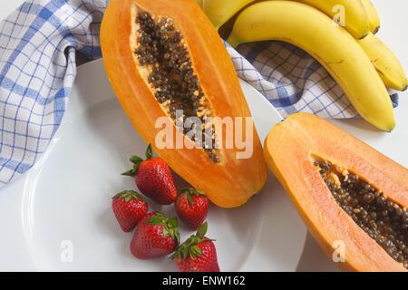 Papaya, Bananen, Erdbeeren, auf einem Küche Zähler nach oben mit einem weißen Teller und Küchentuch im Hintergrund. - Stockfoto