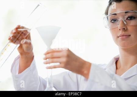 Wissenschaftler, die Flüssigkeit in einen Trichter gießen - Stockfoto