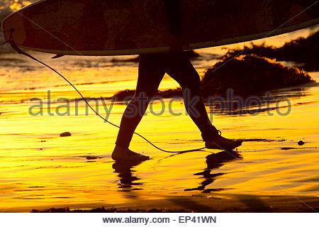 Ein Surfer-Füße, Beine zu Fuß bis an den Strand nach einem langen Tag des Surfens der California coast mit Surfbrett - Stockfoto