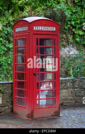 Lustiges kleines Mädchen verstecken und spielen in einer traditionellen englischen Telefonzelle im Retro-Vintage - Stockfoto