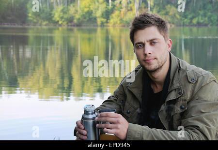 hübscher attraktiver Mann am See auf schöne Natur Hintergrund entspannen Konzept
