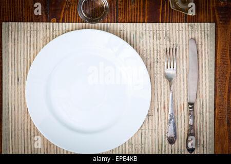Tischdekoration für zwei Personen mit leeren Teller - rustikalen Holztisch - Stockfoto