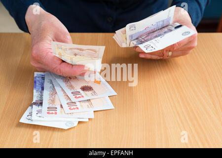 Eine ältere Person Hand hält englisches Geld in Sterling zehn und zwanzig Pfund Banknoten GBP zu kaufen und zu zahlen - Stockfoto