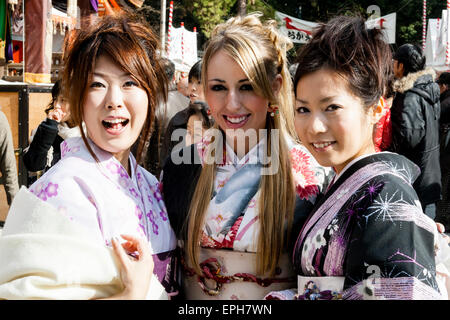 Drei lächelnde junge Frauen in Kimono im Freien posieren für Bild. Äußere zwei sind Japaner, mittlere Frau ist kaukasisch - Stockfoto