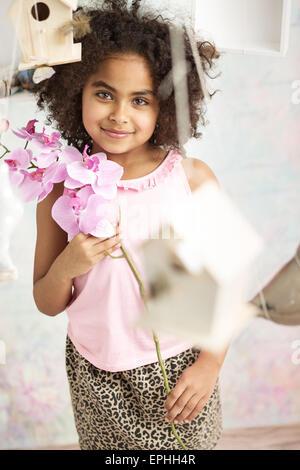 Hübsche kleine Dame, die eine Blume - Stockfoto