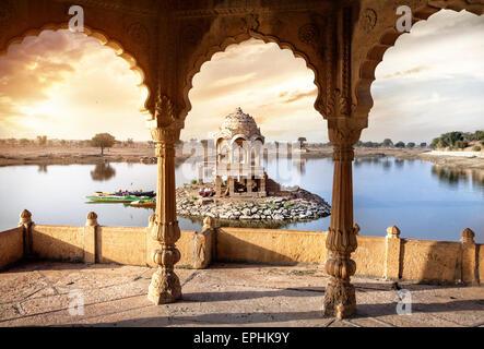 Bögen und Tempel in Gadi Sagar See bei Sonnenuntergang Himmel in Jaisalmer, Rajasthan, Indien - Stockfoto
