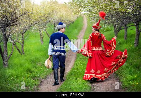 Paar im kasachischen Kostüm herumlaufen Frühjahr blühen Apfel Garten Almaty, Kasachstan, Zentralasien - Stockfoto