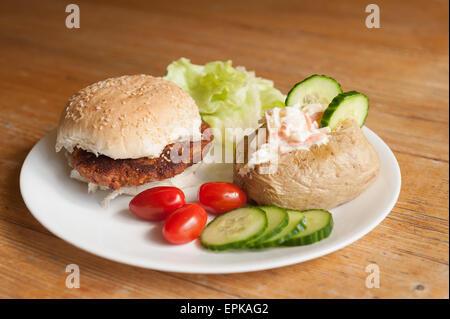 Vegetarische Kidneybean Burger in Sesam Brötchen mit Ofenkartoffel Krautsalat Tomaten Salat Gurkenscheiben als gesunder - Stockfoto