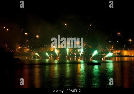 Feuerwerk. Buntes Feuerwerk mit Valletta Hintergrund, große Explosion, Haus Licht, Grüne Spiegelungen auf dem Wasser - Stockfoto