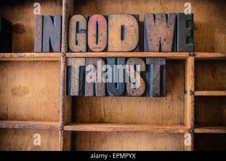 Die Phrase IN GOD WE TRUST in Vintage Holz Buchdruck Typ in einer Schublade aus Holz Art geschrieben. - Stockfoto
