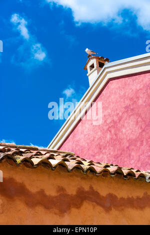 Bunten Wänden, rosa & Orange blau bewölktem Himmel kontrastiert, eine Möwe sitzt auf einem Schornstein bietet eine - Stockfoto
