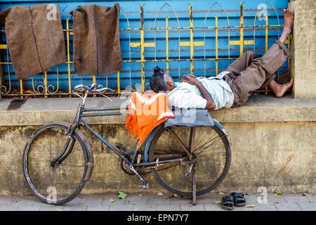 Mumbai Indien Asien Fort Mumbai Kala Ghoda D'Mello Rd Mann schlafen in öffentlichen Fahrrad - Stockfoto