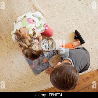 Draufsicht der zwei kleine Kinder sitzen auf Boden mit Farbe Kreide gezeichnet. - Stockfoto