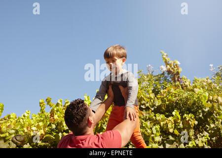 Schuss der Vater seinen Sohn hoch in die Luft heben. Glücklicher Vater und Sohn spielen im Freien an einem sonnigen - Stockfoto