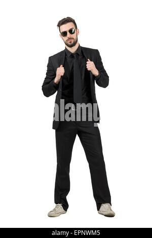 Geheimnisvoller bärtigen Mann im schwarzen Anzug und weiße Turnschuhe mit Kragen. Ganzkörper-Länge-Porträt über - Stockfoto