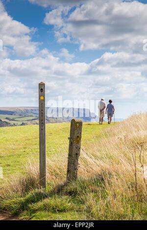 Ein Mann und Frau paar zu Fuß der Klippen hinter einen öffentlichen Fußweg anmelden die Dorset Jura-Küste in der - Stockfoto