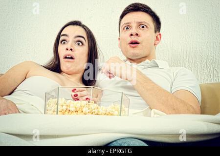Verängstigten jungen attraktives Paar, sitzen auf der Couch im Wohnzimmer zu Hause abgedeckt mit Decke und beobachten - Stockfoto