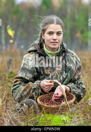Junge Frau pick Cranberry auf einem Moor. - Stockfoto