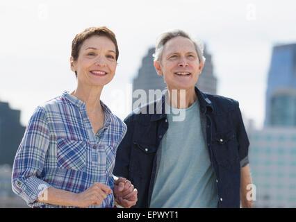 Lächelnd älteres paar zu Fuß in die Stadt - Stockfoto