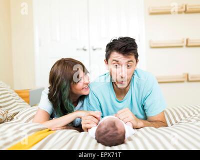 Glückliche Eltern spielen mit Baby (6-11 Monate) auf Bett - Stockfoto