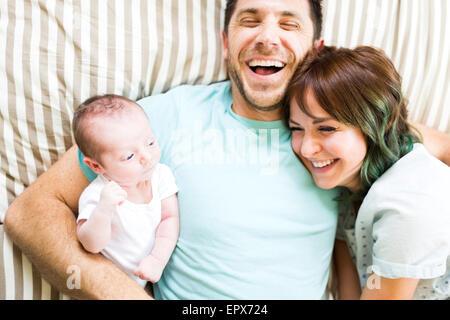 Glückliche Eltern mit Baby (6-11 Monate) auf Bett liegend - Stockfoto