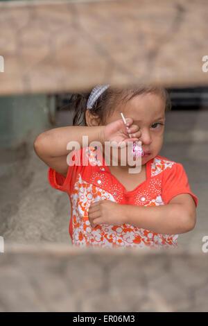 Kleines Mädchen mit Süßigkeiten Saugnapf wischte ihre Augen nach Weinen gesehen durch einen Zaun in Guatemala - Stockfoto