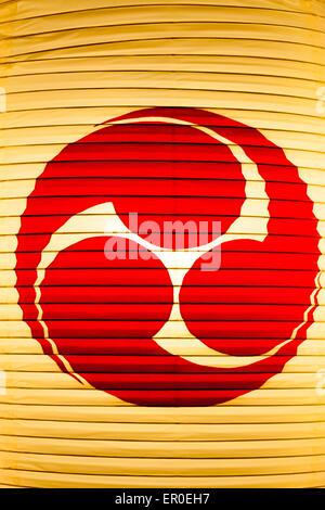 Nahaufnahme von der beleuchteten japanischen Shinto-Papierlaterne, Chochin, mit rotem kreisförmigem Emblem auf, - Stockfoto