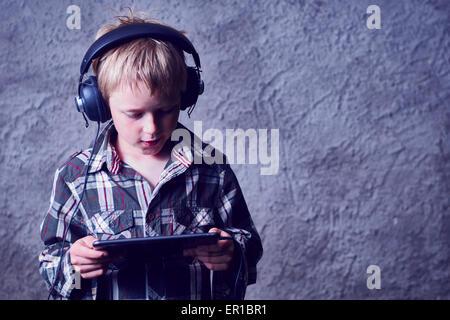 Kind blond Boy Musikhören mit Kopfhörer und mit digital-Tablette - Stockfoto