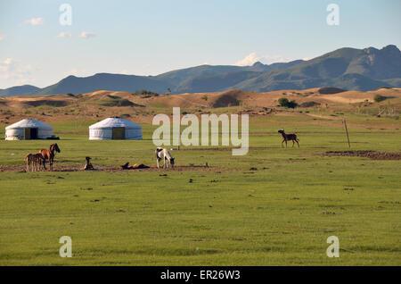 Jurten und Pferde in der Steppe vor Sanddünen und einer Bergkette in der Tov Provinz, Mongolei - Stockfoto