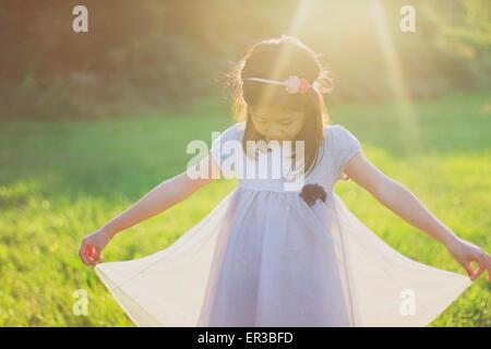Mädchen hält den Saum ihres Kleides - Stockfoto