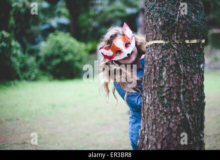 Teenager mit Fuchs Maske versteckt sich hinter einem Baum - Stockfoto