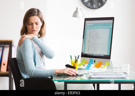 Frau bei der Arbeit leiden unter Schmerzen in der Schulter. - Stockfoto
