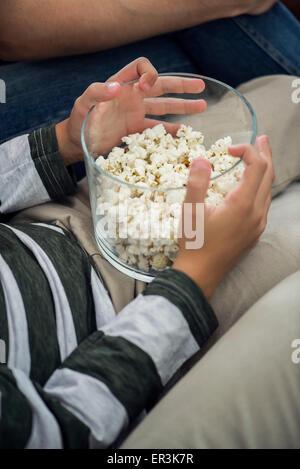 Kind Holding Schüssel Popcorn auf Schoß, beschnitten - Stockfoto
