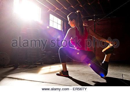 Eine Sportlerin erstreckt sich in einer Crossfit Gym. - Stockfoto