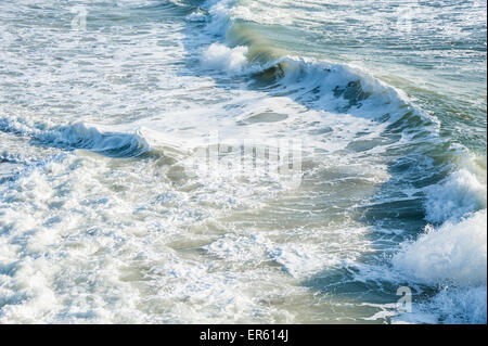 Am frühen Morgensonnenlicht beleuchtet die schaumigen weißen Schaum der brechenden Wellen am Strand von Florida - Stockfoto