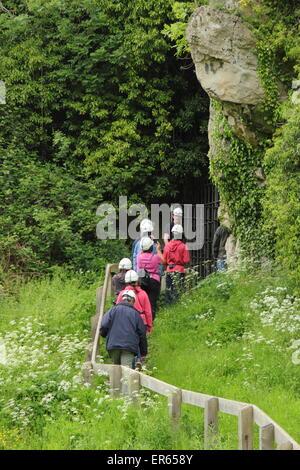 Besucher betreten eine Höhle bei einem Rundgang durch Creswell Crags an der Grenze von Derbyshire und Nottinghamshire, - Stockfoto