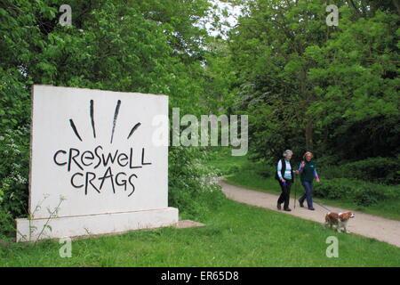 Besucher zu Fuß einen Hund nach dem Ortseingangsschild, Creswell Crags an der Grenze von Derbyshire und Nottinghamshire, - Stockfoto