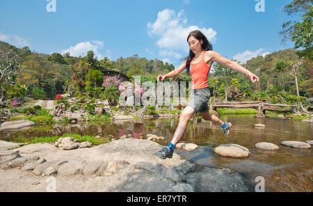 Frau auf Kobbel Steinen über einen kleinen Teich springen - Stockfoto