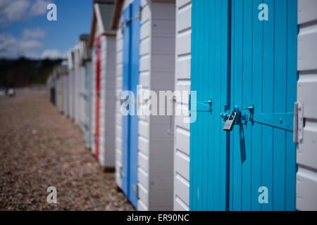 Eine Reihe von Strandhütten mit bunten Türen am Kiesstrand, Devon, UK - Stockfoto