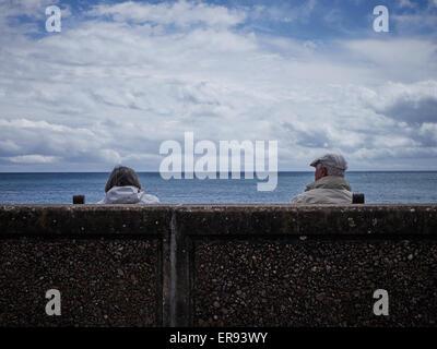Ein paar sitzen hinter dem Deich mit Blick auf das Meer - Stockfoto